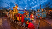 A colorful train with circus animals in Casey Jr. Splash 'N' Soak Station at night