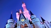 Cinderella Castle with its top spires bathed in pink light at night
