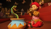 A snake charmer doll, charming a snake out of its pot