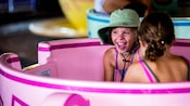 A delighted girl and her friend inside a spinning tea cup at the Mad Tea Party attraction