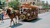 A conductor drives a trolley car, pulled by a horse, that's filled with Guests