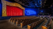 Inside a concert hall with rows of theater seats and curtained screen at Mickey's PhilharMagic