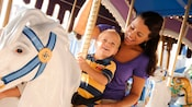 A mom and her young son enjoy riding a horse at Prince Charming Regal Carrousel