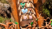 Guests riding in a hollow log drop down the face of Splash Mountain