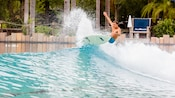 A male surfer makes a radical cutback on the lip of a wave at Disney's Typhoon Lagoon Surf Pool