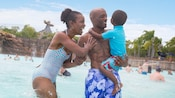 A couple stand in a huge wave pool laughing with their young son