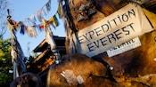 Une banderole sur un mur de pierre avec l'inscription Expédition Everest à côté de drapeaux himalayens suspendus par une corde