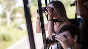 Guests peer through binoculars from an open-air bus