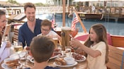 A family of 5 enjoy a lobster dinner seated at a table on outdoor deck of The BOATHOUSE