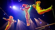 Three acrobats in orange monkey outfits perform on gymnastic rings