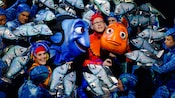 Performers in brightly colored fish costumes in a Broadway-style show called Finding Nemo – The Musical