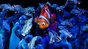 Marlin surrounded by fish in a scene at Finding Nemo - The Musical