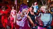 A group of women enjoy lively nighttime dancing, some of them with face paint