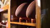 A row of wooden shelves with one shelf holding 2 American footballs on tees