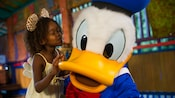 A young female Guest kisses Donald Duck during an in-park meeting with the popular Disney Character