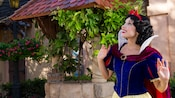 Three little girls run playfully around a seated and delighted Snow White
