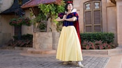 Snow White stands on a cobblestone road and clasps her hands at Meet Snow White in Germany at Epcot