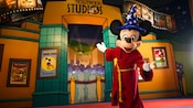 Sorcerer Mickey stands in front of a painted backdrop of the Disney's Hollywood Studios