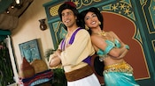 Aladdin and Princess Jasmine standing back-to-back in Adventureland at Magic Kingdom park