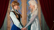 Princess Anna and Queen Elsa from the Disney film 'Frozen' hold hands as they greet each other