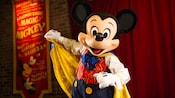 Master Magician Mickey grabs his cape while onstage at Town Square Theater in Magic Kingdom park