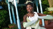 A young girl and her older sister skip around a seated and delighted Princess Tiana