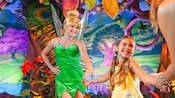 Tinker Bell reaches for the hand of an excited little girl from the audience.
