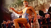 Man in wrestling-inspired costume marches with an exaggerated step in front of a chorus line of men at  Cirque de Soleil – La Nouba