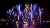 Blue and white fireworks explode over World Showcase Lagoon