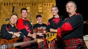 Band members dressed in kilts perform on stage at Epcot