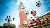 An enthusiastic man in stripes juggling soccer balls in a courtyard of the Italy Pavilion at Epcot