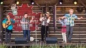 Musicians from TradNation playing instruments on stage during a performance at the Canada Pavilion