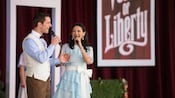 A well-dressed couple from Voices of Liberty a cappella choir hold hands as they sing a duet on stage