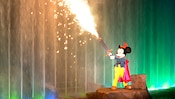 Sparks shoot from Mickey's sword by a wall of colored water in the Fantasmic nighttime spectacular