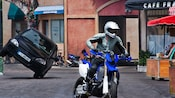 A motorcyclist is pursued by a speeding car at the Lights, Motors, Action! Extreme Stunt Show