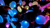 Glowing Mickey Ears light up as they sit piled together at night