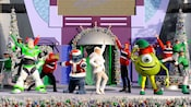 The cast of A Totally Tomorrowland Christmas performs in holiday attire with Buzz Lightyear and Mike Wazowski.
