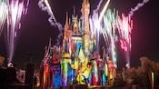 Vibrant art featuring Disney storytelling projected onto Cinderella Castle amid evening fireworks