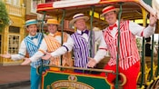 A barbershop quartet in pinstripe vests in and around a trolley at Magic Kingdom park