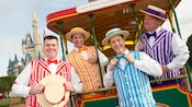 The Dapper Dans barbershop quartet pose on a trolley car with Cinderella Castle in the background