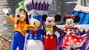 Goofy, Donald Duck, Mickey Mouse and Minnie Mouse posing together in front of Cinderella Castle