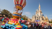 Mickey and Minnie in a parade float shaped like a hot-air balloon wave to Guests and, beyond, Cinderella Castle