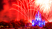 Fireworks light up the colorful sky above Cinderella Castle that's bathed in a different hue