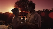 A couple embraces while holding wine glasses as the sun sets directly next to the Tree of Life