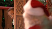 A gleeful young boy peering around a corner to discover Santa Claus waiting in the foreground
