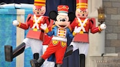 Mickey Mouse dressed in seasonal holiday clothing dancing in formation with 2 life-size nutcrackers