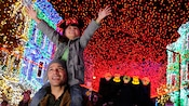 A young girl reaching into a sky of shining holiday lights while sitting on her father's shoulders