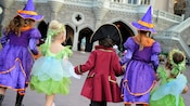 Five kids in different costumes walking into Mickey's Not-So-Scary Halloween Party