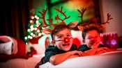 Two young boys smiling while wearing light-up Rudolph the Red-Nosed Reindeer noses, ears and antlers