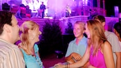 A family attending Night of Joy smiles toward one another in between songs during a performance